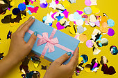 female hands holding blue gift box with festive pink bow on a yellow background with holographic multicolored confetti