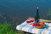 red wine and fruit basket , picnic on the lake