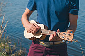 unrecognizable young man playing on a hawaiian guitar on a lake background