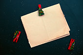rough blank sheet of vintage paper with festive cloth pin on a black background
