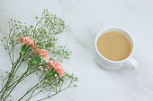 flowers and cup of drink   on a marble background copy space