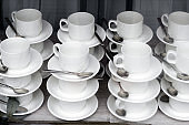 pattern of pairs of mugs and plates with spoons in the window of the tableware store