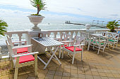 ables and chairs on  terrace of beach restaurant on the embankment