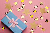 beautiful blue gift box with pink satin ribbon with bow on a pink background with golden stars sequins