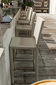 row of wicker chairs on the street terrace of the restaurant