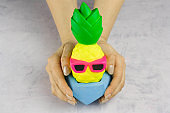 girl's hands with bright pineapple with sunglasses in concrete pot