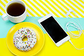 donut on a yellow plate and coffee cup  on a blue and yellow background