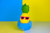 funny pineapple toy in concrete pot  on blue and yellow