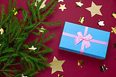evergreen christmas tree branches, gift box and starry confetti on a red background