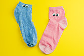 pink and blue  socks with googly eyes isolated on yellow background