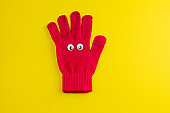 red  glove  with googly eyes isolated  on a yellow background