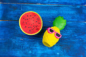 funny pineapple toy in sunglasses and squishy toy watermelon on a blue wooden background