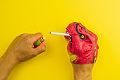 dinosaur lights a cigarette,  concept of a harmful lifestyle