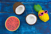 funny pineapple toy in sunglasses,watermelon  and coconut on a blue wooden table
