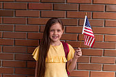 girl smiling and holding American flag