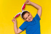 smiling adorable little boy wearing bunny ears isolated over yellow background