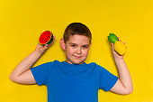 little boy holding fruits in hands  isolated on yellow background