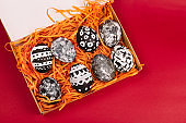 collection of dyed black and white easter eggs in box on a red background