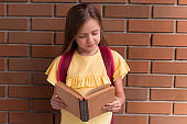 portrait of a little beautiful girl with a backpack holding book