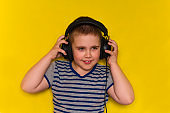 beautiful cute young boy  with  big black headphones isolated on yellow vibrant background