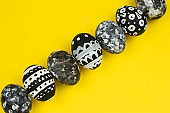 collection of dyed black and white easter eggs on a yellow background