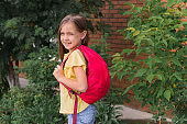 beautiful  little girl with a backpack on the background of a brick wall and green bushes
