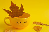 cup with cute smile face  and maple dried autumn leaves on a yellow background