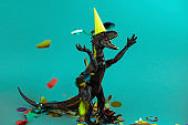 big black  dinosaur wearing yellow  party hat  and falling confetti