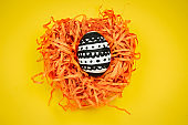dyed black and white easter egg with geometric patetrn in decorative nest  on a yellow background