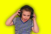 beautiful positive boy in stripped  t-shirtwith headphones    isolated on yellow background