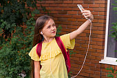 beautiful little girl with a backpack using a mobile phone