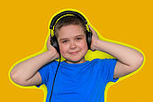 beautiful cute young boy in blue t-shirt with  big black headphones isolated on yellow vibrant background