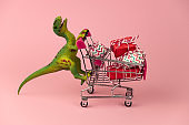 funny green dinosaur toy with shopping cart full of present boxes