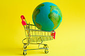 metal shopping cart with a model of the planet Earth inside