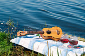 hawaiian guitar and two red wine glasses