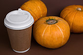 pumpkins and spicy pumpkin latte in a paper cup