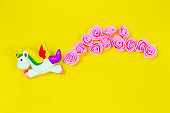 creative still life with flying unicorn and tropical flowers isolated on a yellow background