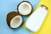 coconut and mock upwhite  plastic  bottle  on a yellow and blue background