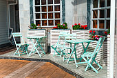 vintage blue furniture and blooming potted red flowers  on the restaurant terrace on a sunny day