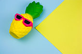 summer vibrant blue and yellow  background with funny pineapple toy in sunglasses, copy space