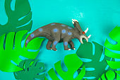 dinosaur toy on blue background with green paper cut tropical leaves