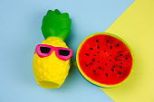 ummer vibrant blue and yellow  background with funny pineapple toy in sunglasses and squishy toy watermelon