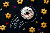 donut meteorite with googly eyes among the stars of cookies on a black chalkboard background