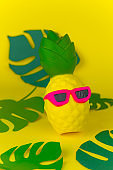 squishy toy pineapple in sunglasses on yellow background