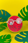 squishy toy watermelon in  glasses on yellow background