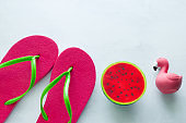 pink beach flip flops  and squishy toy watermelon  and flamingo  on white  background