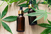 natural herbal hemp essential oil in a glass bottle and marijuana green leaves