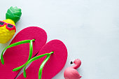 pink beach flip flops  and squishy toy pineapple in sunglasses and flamingo