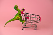 green dinosaur toy with shopping cart