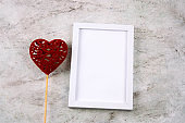 empty white frame with place for text and fabric stuffed toy in a shape of heart